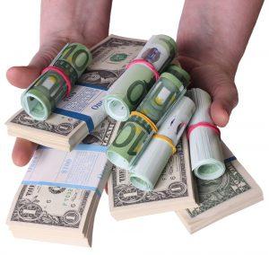 Hands holding cash in multiple currencies depicting cash flow